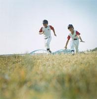 芝生を走る2人の野球少年 日本人