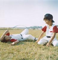 芝生でくつろぐ2人の野球少年 日本人