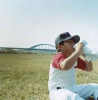 芝生に座り飲み物を飲む野球少年 日本人
