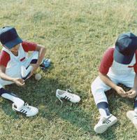 芝生で休憩する2人の野球少年 日本人