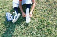 芝生で靴紐を結ぶ野球少年 02299002296| 写真素材・ストックフォト・画像・イラスト素材|アマナイメージズ