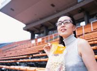 観客席でポップコーンを食べる40代の日本人女性 02299002341| 写真素材・ストックフォト・画像・イラスト素材|アマナイメージズ