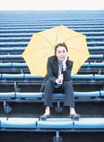 観客席に座りほおづえをついて黄色い傘を差す40代の日本人女性
