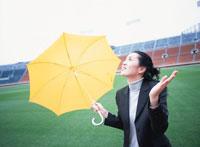 傘を差し手を広げる40代の日本人女性