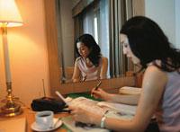鏡の前でペンを持つ40代の日本人ビジネスウーマン