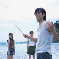 海辺で遊ぶ男性と2人の女性 日本人