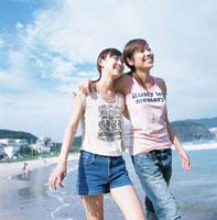 肩を組んで砂浜を歩く2人の日本人女性