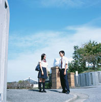校門そばで話をする男子高校生と女子高校生
