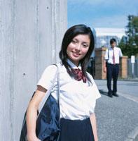 カバンを持った女子高校生と校門前の男子高校生
