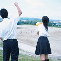応援する男子学生と女子学生の後姿