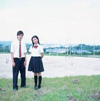 グラウンドに立つ男子学生と女子学生 02299002717| 写真素材・ストックフォト・画像・イラスト素材|アマナイメージズ