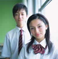 教室の窓辺に立つ女子高校生と男子高校生
