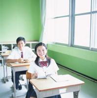 教室の席につく女子高校生と男子高校生
