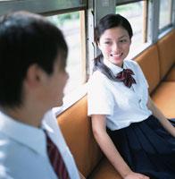 電車の座席に座る男子高校生と女子高校生