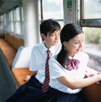 車窓から外を眺める男子高校生と女子高校生