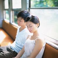 電車の座席に座るカップル