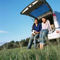 自動車のトランクに座る日本人カップル