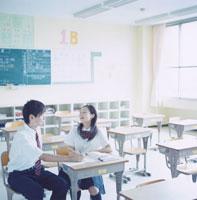 教室の椅子に座り勉強する女子高校生と男子高校生