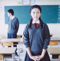 教室で手を組み合わせる女子高校生