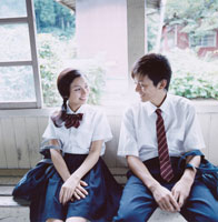 駅舎のベンチに座る女子高校生と男子高校生