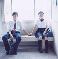 駅舎のベンチに座り手を繋ぐ女子高校生と男子高校生