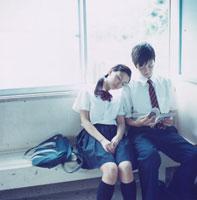 駅舎のベンチで読書する男子高校生と肩に寄り掛かる女子高校生