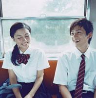 電車の座席に座る女子高校生と男子高校生
