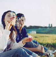 芝生に座りシャボン玉を吹く日本人カップル