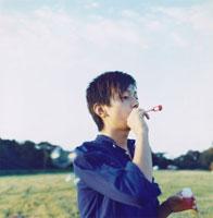 芝生でシャボン玉を吹く日本人男性