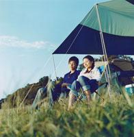 屋外の椅子でくつろぐ日本人カップル