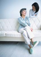 ソファーに座る中高年女性と微笑みあう女の子 02299002864| 写真素材・ストックフォト・画像・イラスト素材|アマナイメージズ