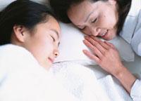 ベットで眠っている女の子と添い寝をするお母さん