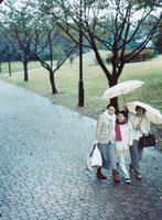 傘をさして歩く三世代の日本人女性