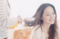 日本人女性の髪に霧吹きをかける美容師の手元