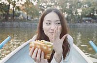 ボートでサンドイッチを食べる日本人女性