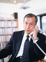 オフィスで受話器を持つ中高年ビジネスマン