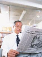 オフィスで新聞を読む中高年ビジネスマン