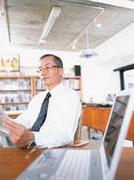 オフィスで新聞を読む中高年ビジネスマンとノートパソコン
