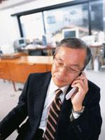 オフィスで携帯電話をかける中高年ビジネスマン 02299003039  写真素材・ストックフォト・画像・イラスト素材 アマナイメージズ