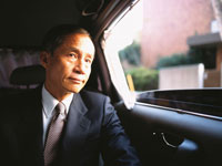 車内の後部座席に座る中高年ビジネスマン