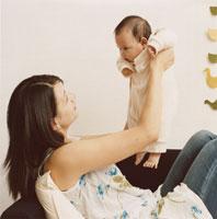 赤ちゃんを抱き上げる母親