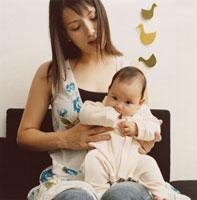 ひざの上に赤ちゃんを乗せた母親