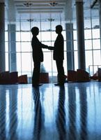 向き合う2人のビジネスマンのシルエット