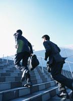 階段を駆け上る2人のビジネスマンの後ろ姿