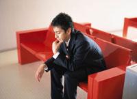 赤いベンチに座る日本人ビジネスマン