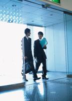 自動ドアから入ってくる2人の日本人ビジネスマン