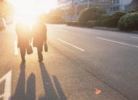 夕日と歩く2人のビジネスマンのシルエット
