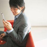 携帯電話を見る日本人ビジネスマン