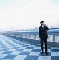 携帯電話をかける日本人ビジネスマン