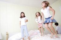 ベットの上で遊ぶ3人の女の子